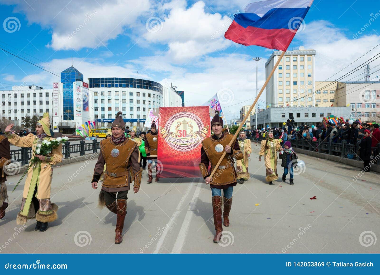 Yakut νεολαία στα εθνικά κοστούμια με τη ρωσική σημαία