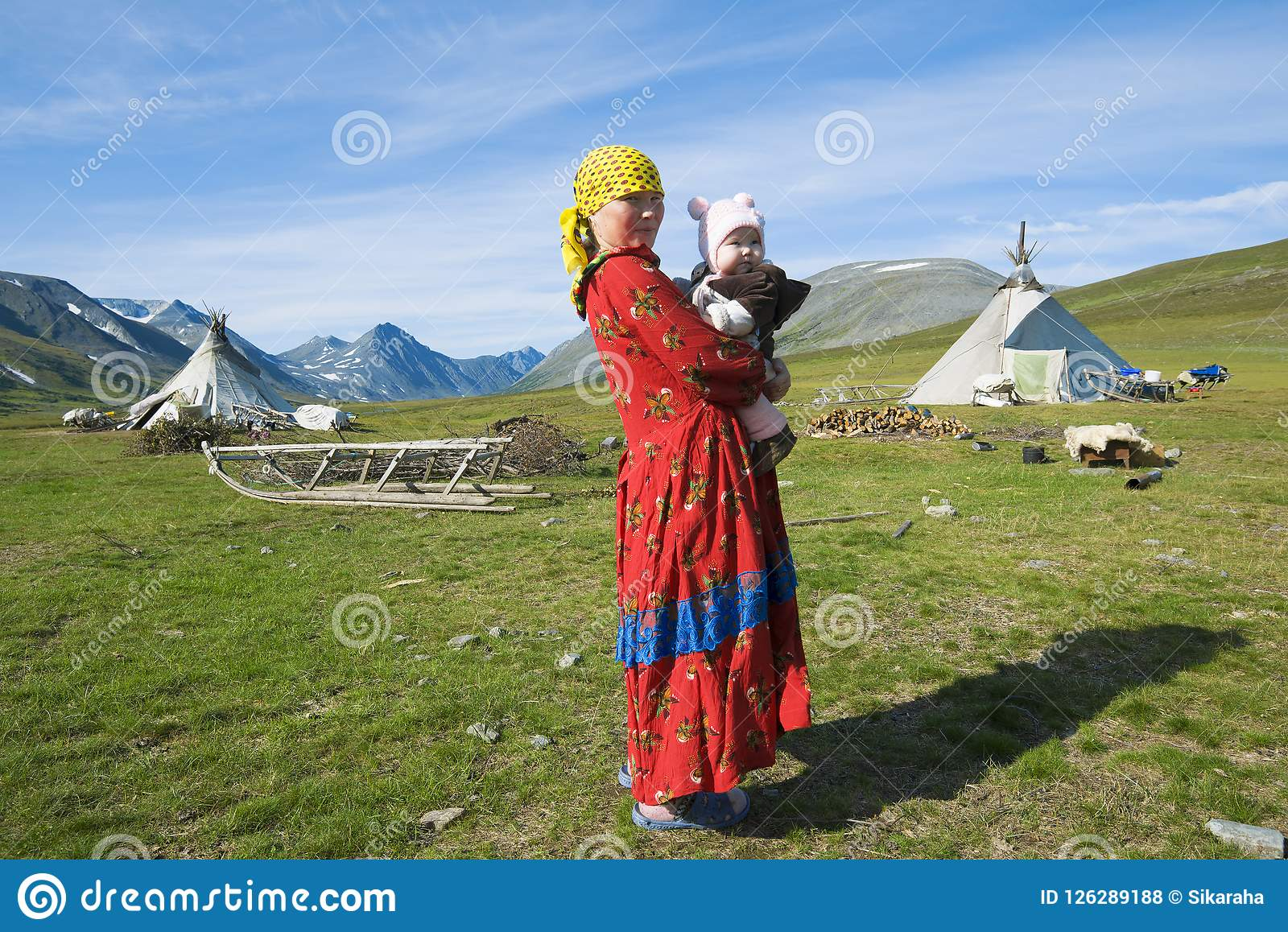 The female Hanty with the child on hands against the background of a settlement of reindeer breeders