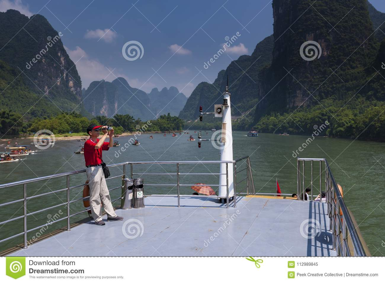 Chinese man in a boat cruising in the Li River and photographing the the tall limestone mountains near Yangshuo in China