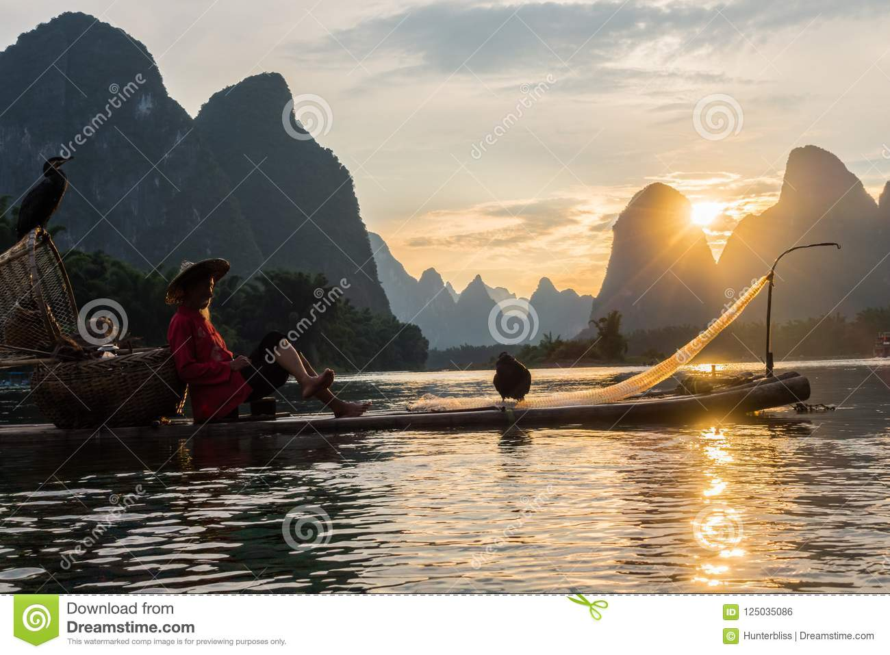 Yangshuo, China Sunset Landscape on Calm River with Villager on