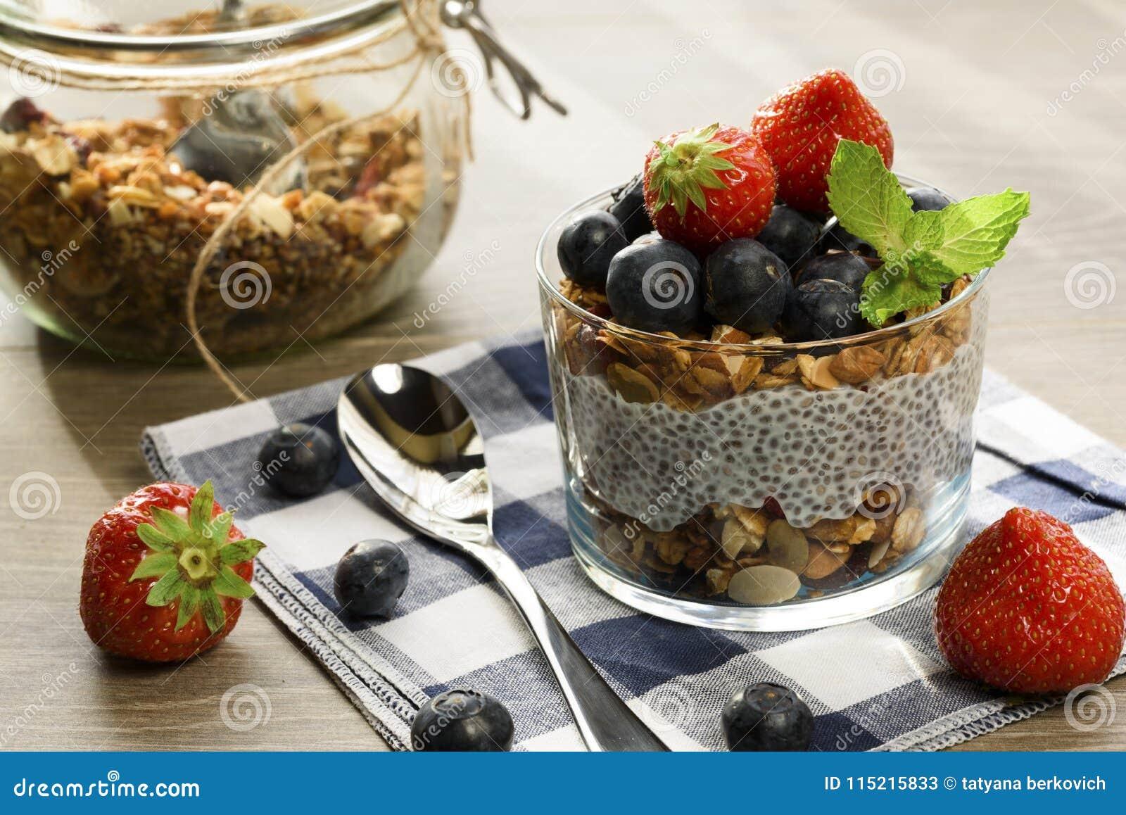 Yaourt avec la granola, les myrtilles fraîches, les graines de chia et l avoine dans un verre au-dessus du fond en bois Fin vers