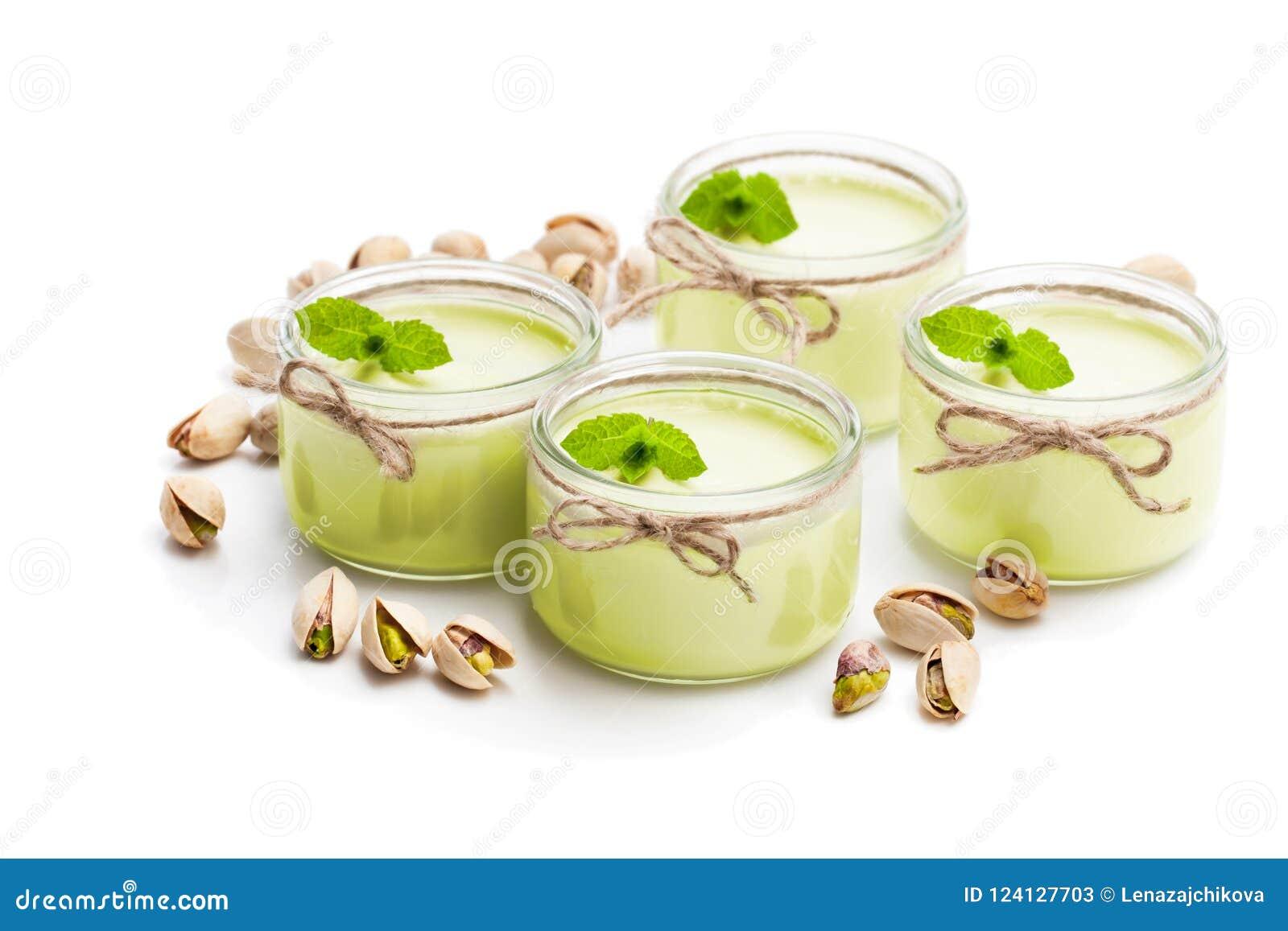 Yaourt naturel de pistache dans un petit pot en verre d isolement sur le blanc