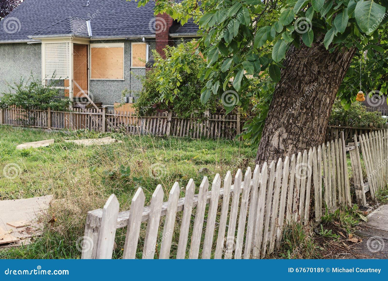 Yarda unkept vacante con la cerca raquítica y subida encima de casa