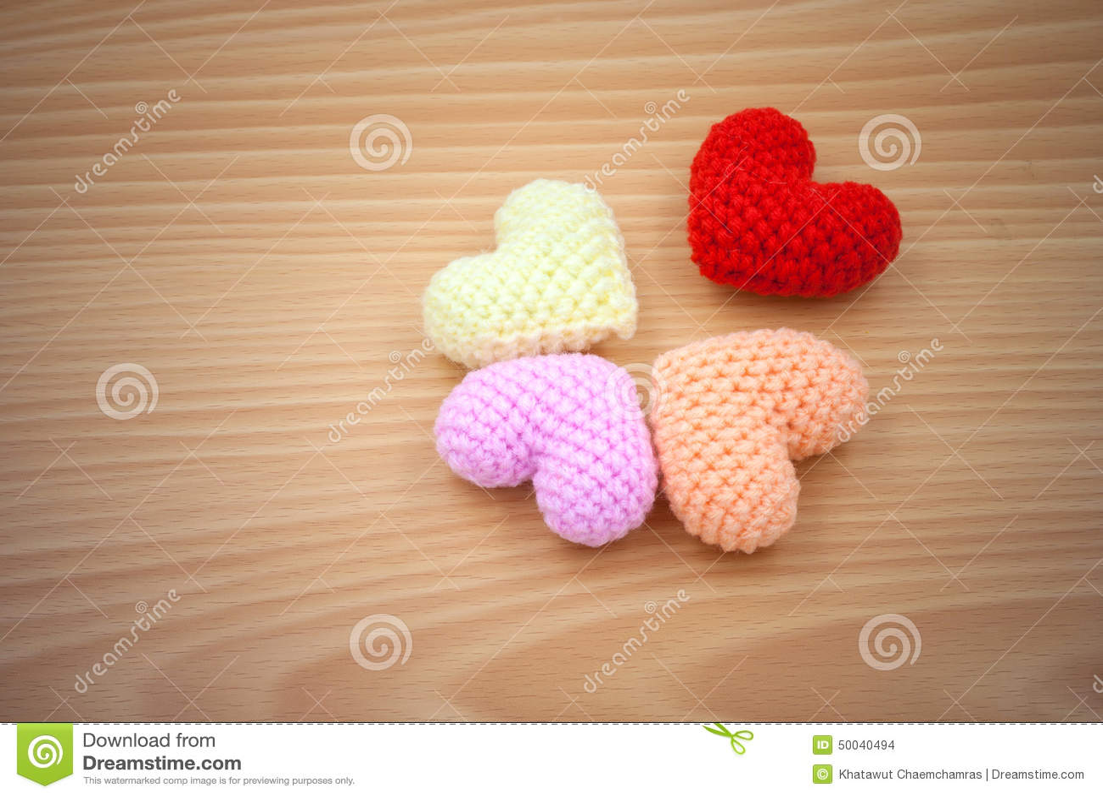 Yarn hearts on wood background