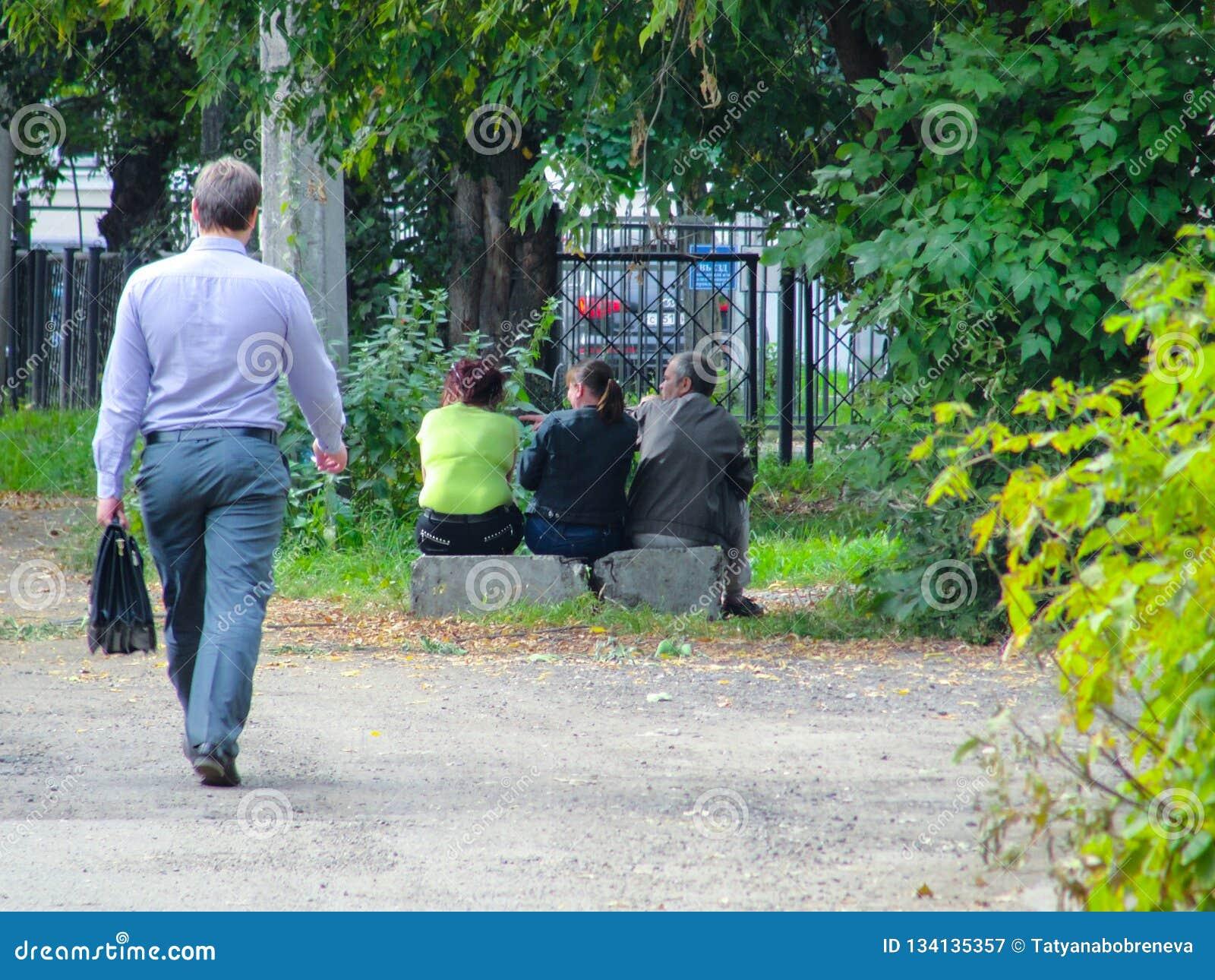 Yaroslavl, Rússia - um homem que passa por três pessoas que sentam-se em uma laje de cimento