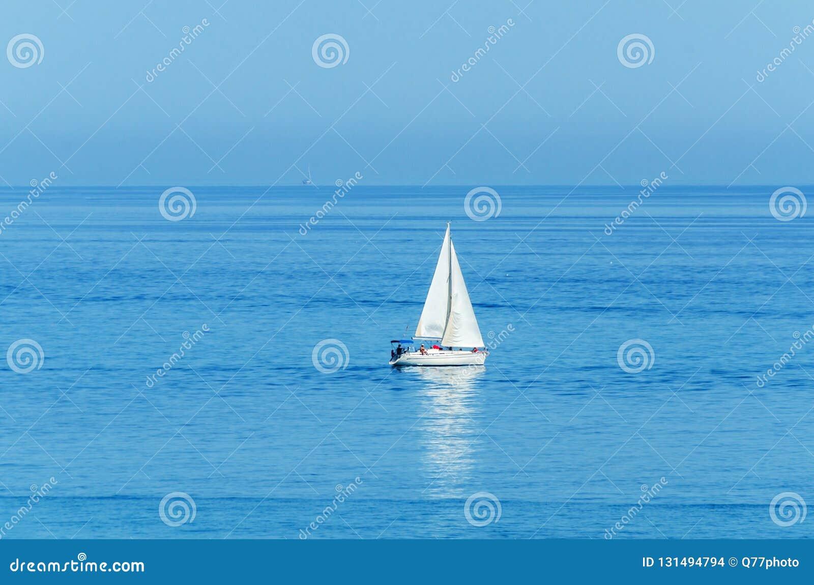 Yate que navega el mar, el cielo claro y el agua azul, deporte recreativo, resto activo