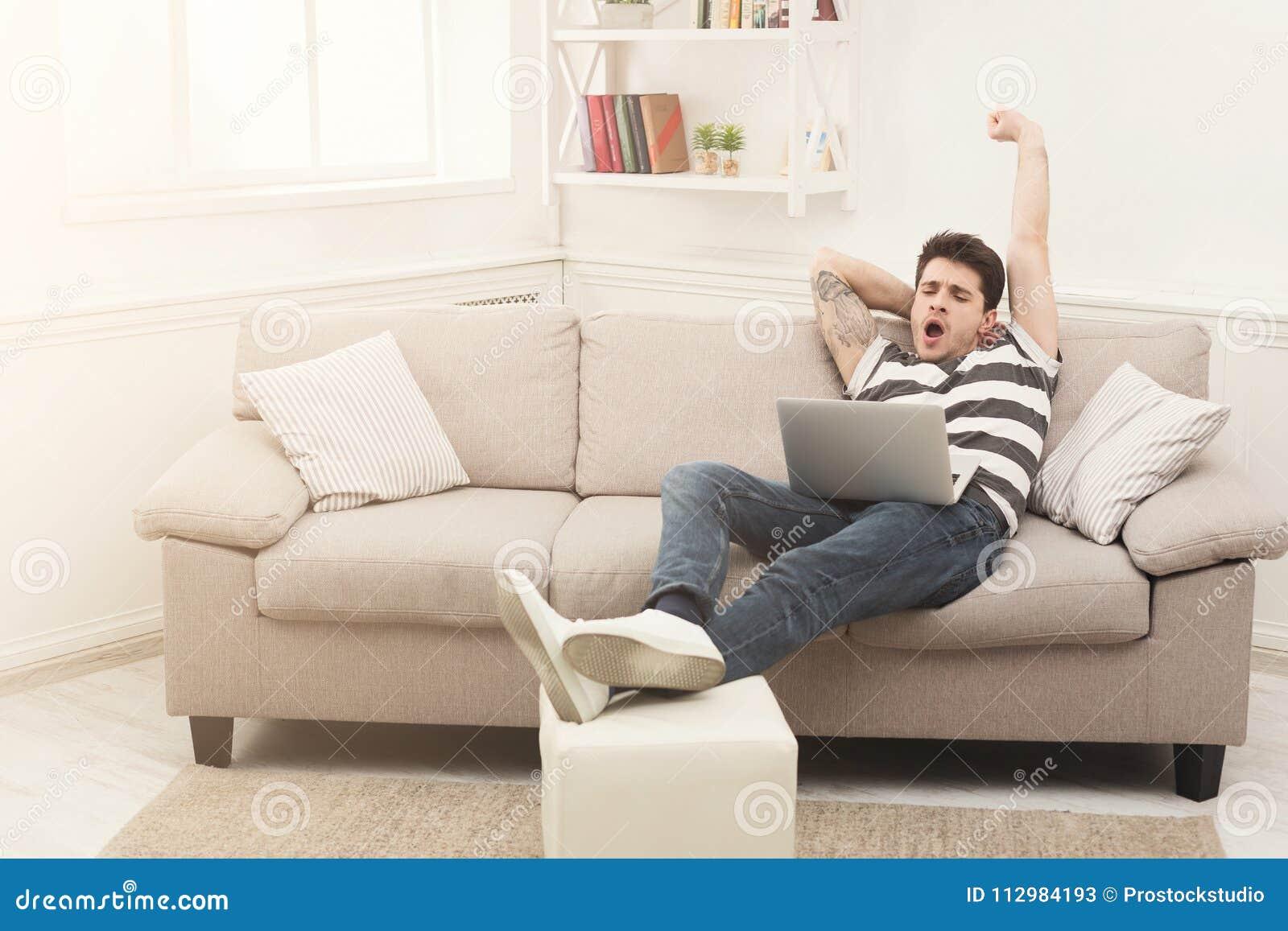 Yawning man using laptop at home