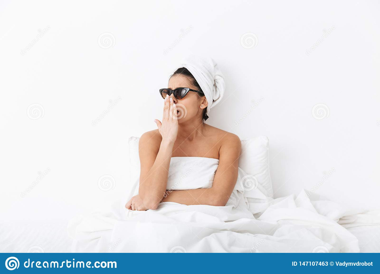 Yawning woman with towel on head lies in bed under blanket isolated over white wall background wearing sunglasses