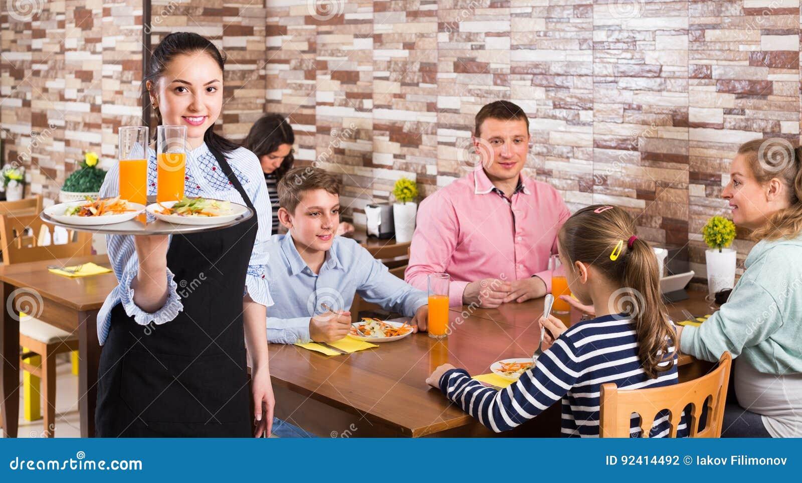 Życzliwa młoda kelnerka wita ciebie rodzinna kawiarnia