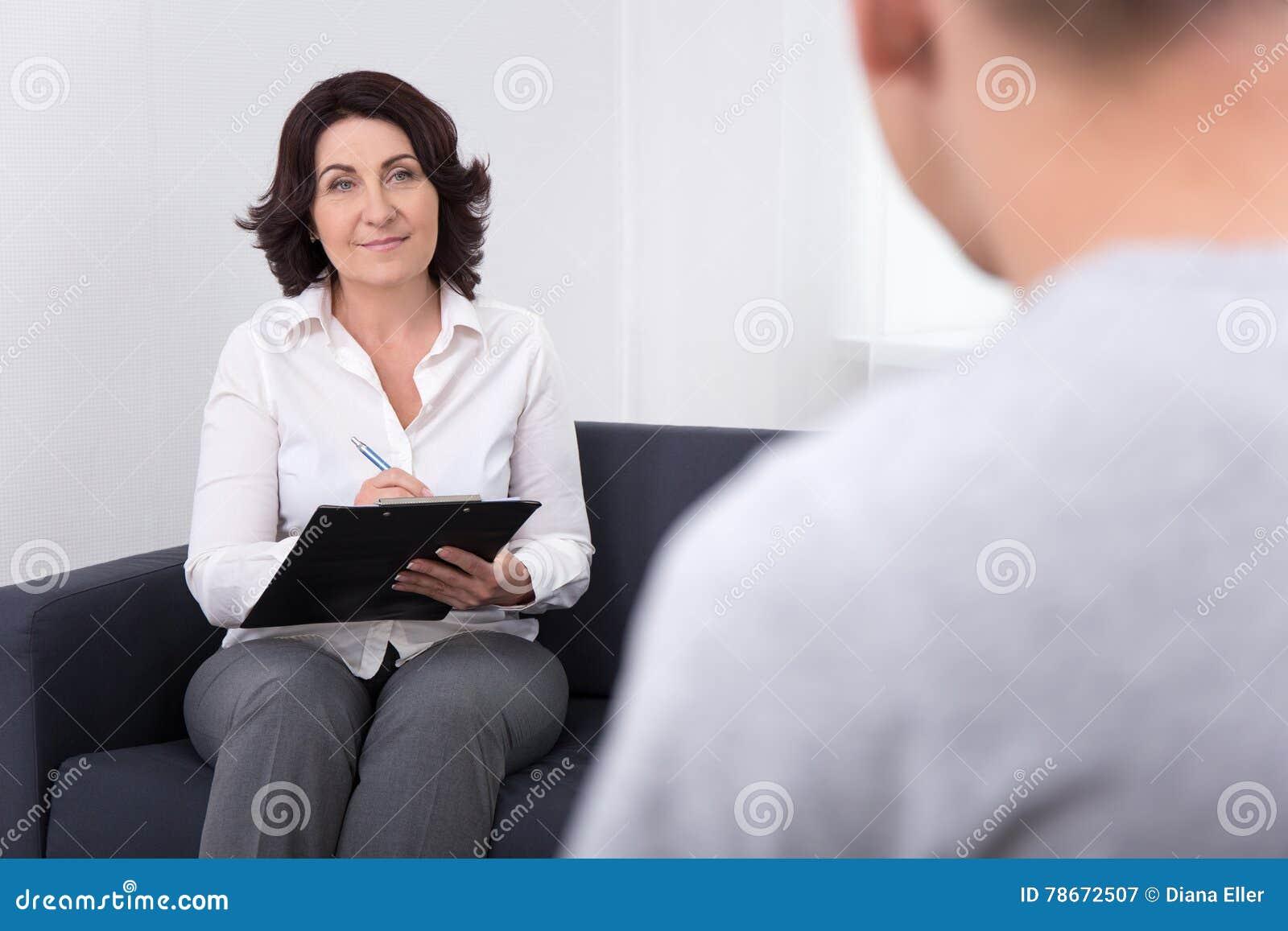 Życzliwy żeński psychiatra egzamininuje jej pacjenta w biurze