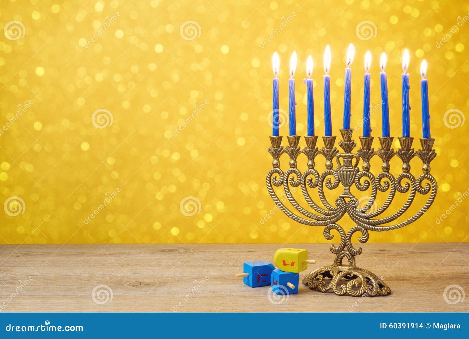Żydowski Hanukkah tło z rocznika menorah i przędzalnianego wierzchołka dreidel nad światła bokeh