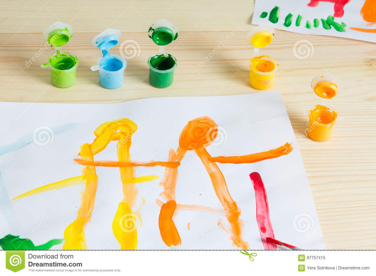 3 year kids drawing happy family picture on the wooden table. To