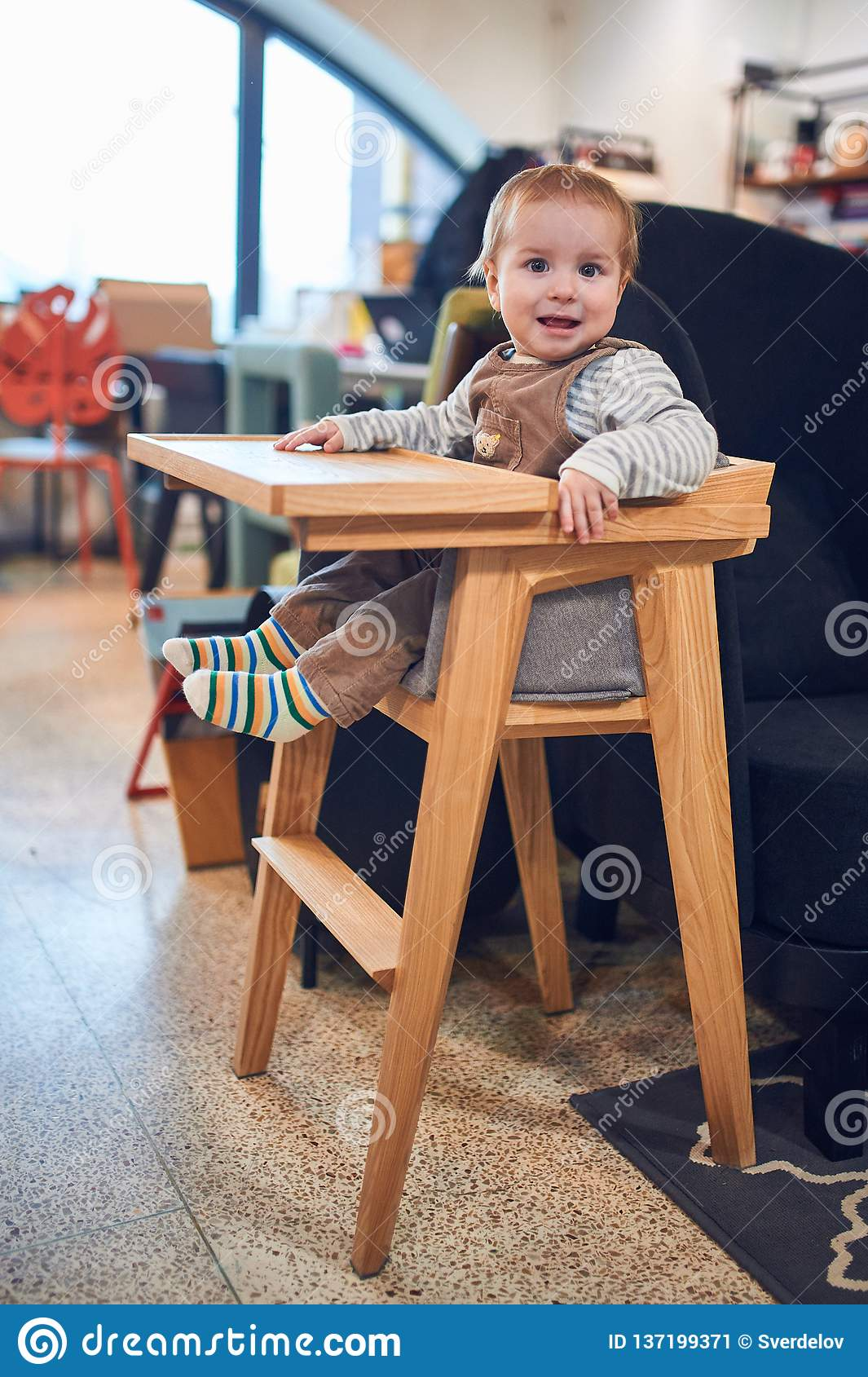 1 Year Old Baby Boy Sitting In Wooden High Chair At Home Stock