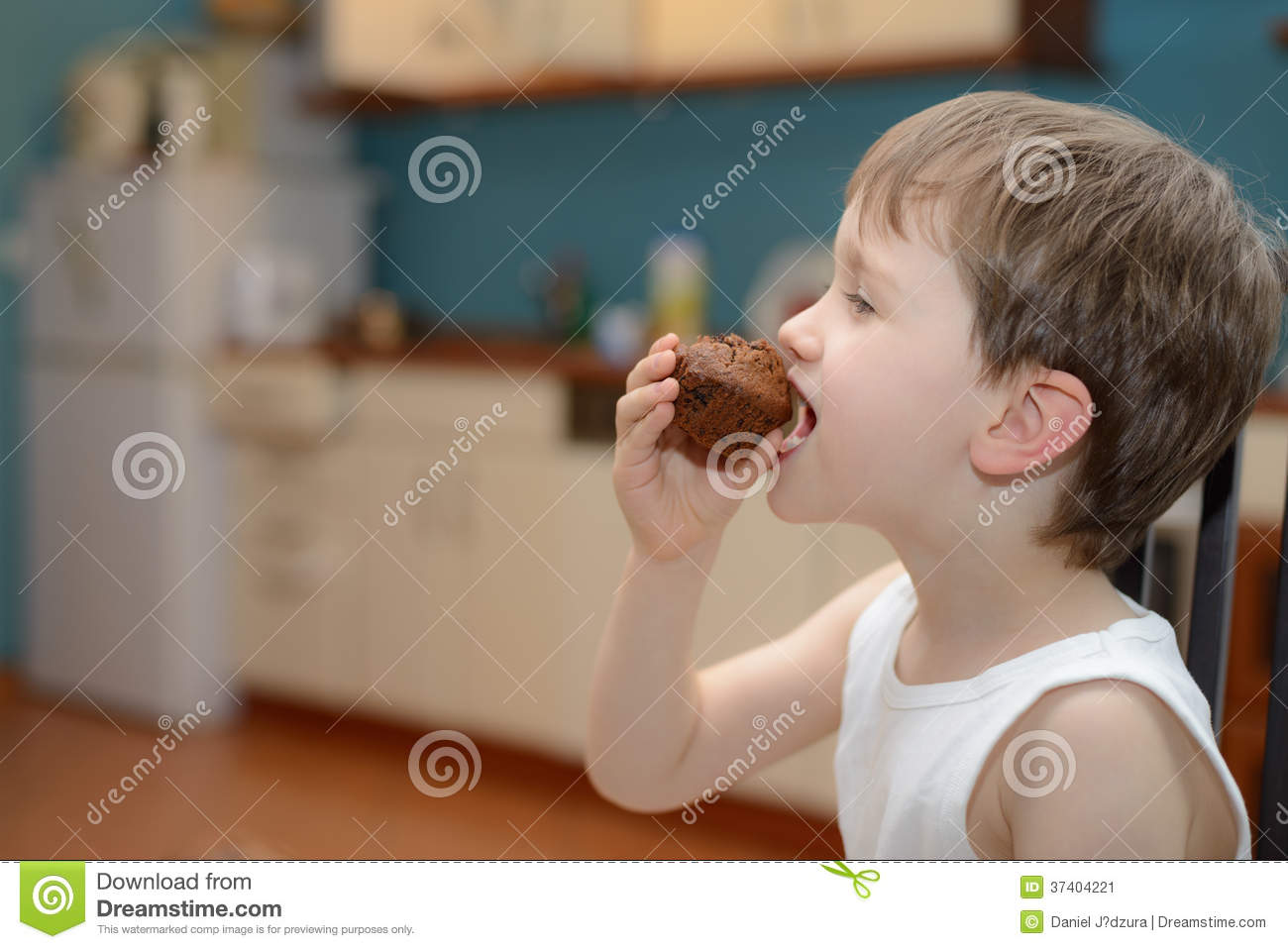 4 year old boy eats chocolate muffin