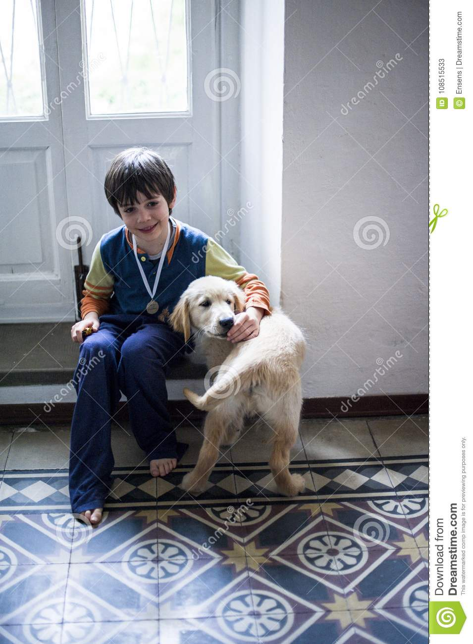 6 year old boy with his golden retriever puppy dog at home
