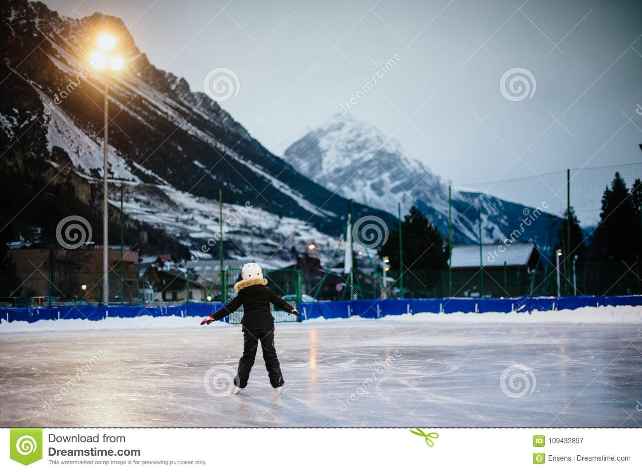 9 year old girl skates on the ice in the evening on an illuminated track