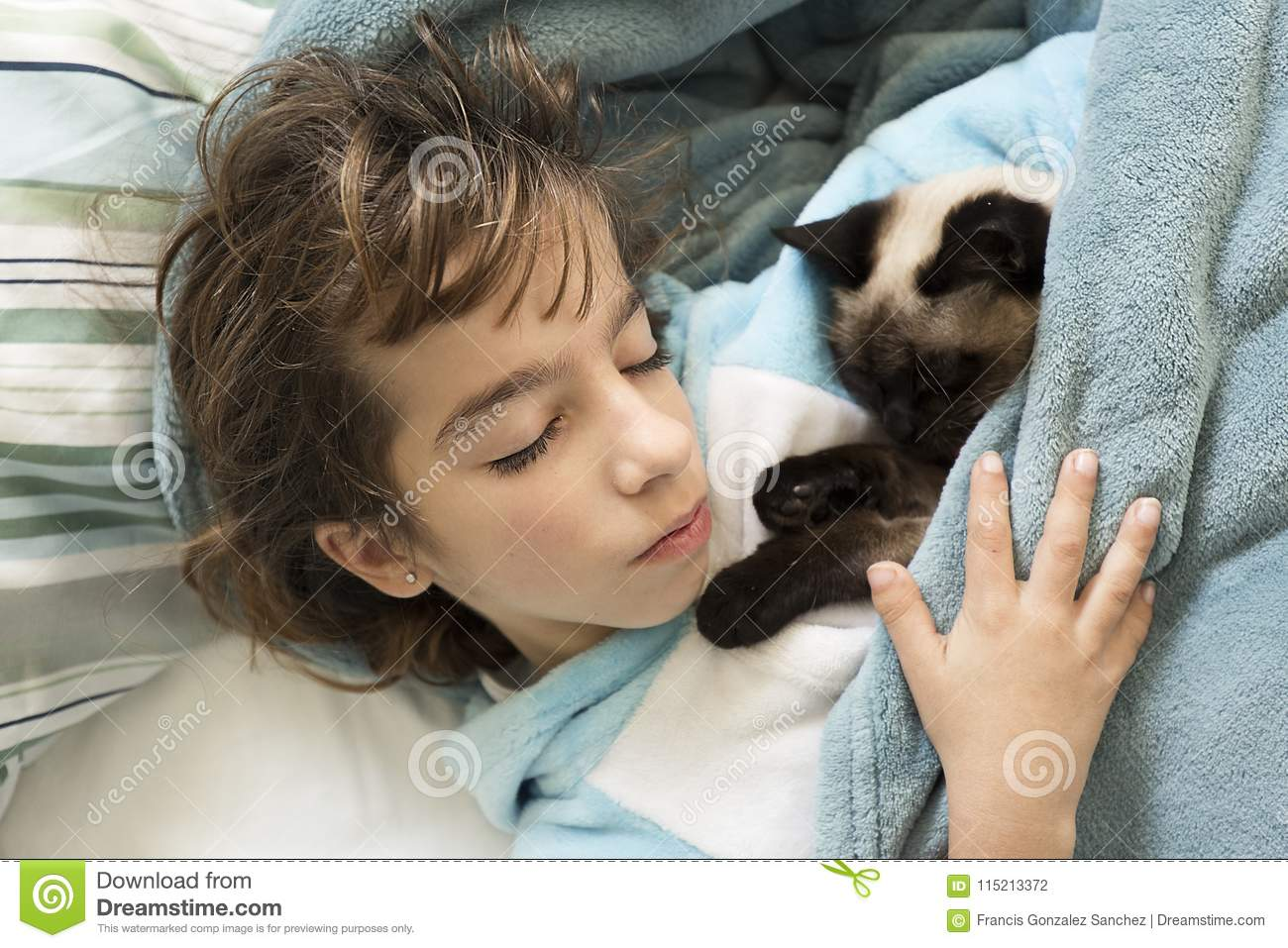10 year old girl sleeping in bed with her cat on top.