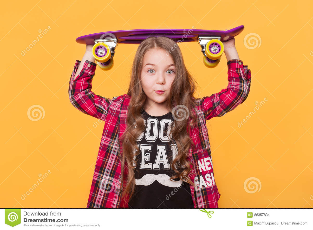dd03e014a6f6 Portrait of a cute 6 year old girl wearing hipster casual clothes posing  with skateboard on head over bright yellow background.