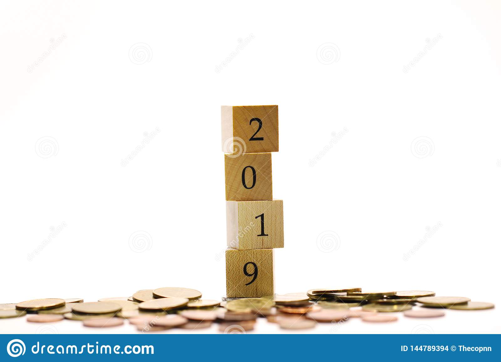 Year 2019 from wooden block surrounding by pile of coins