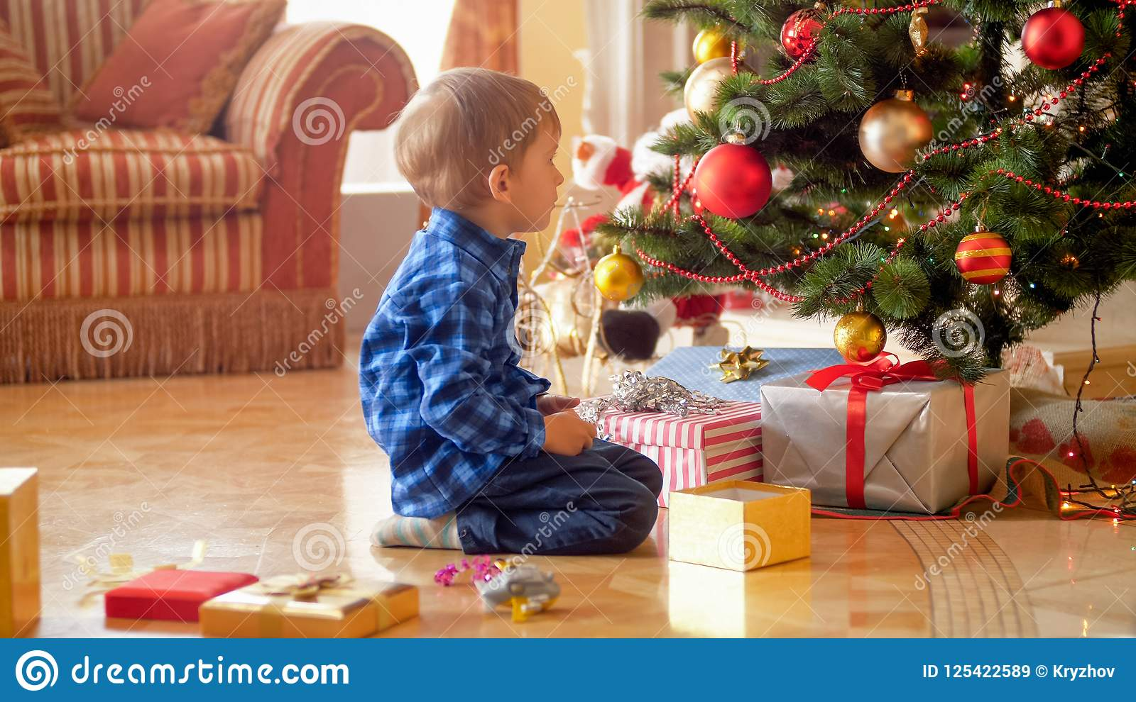 3 Years Old Boy Sitting Under Christmas Tree And Looking On Gifts Presents