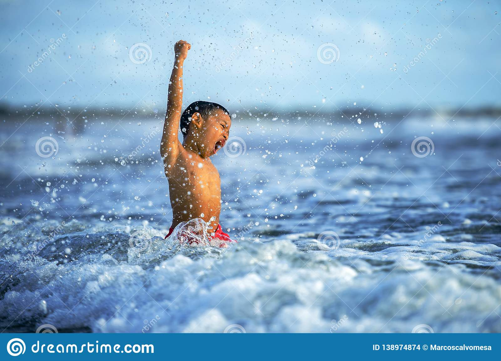 5 years old cute and happy child playing crazy free having fun on the beach splashing on water and sea waves enjoying holidays