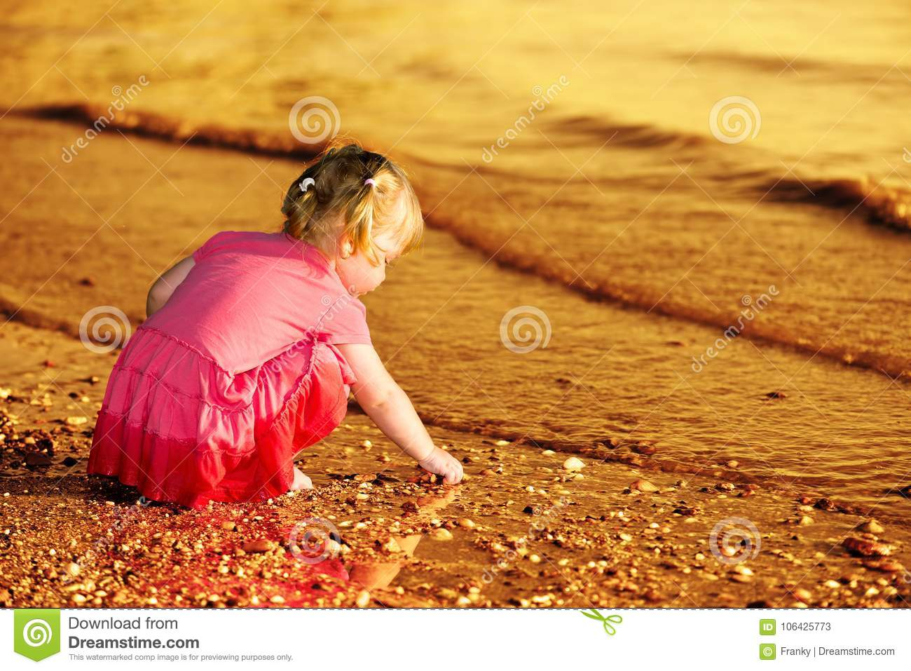 2-3 years old little girl playing with pebbles at the riverbank