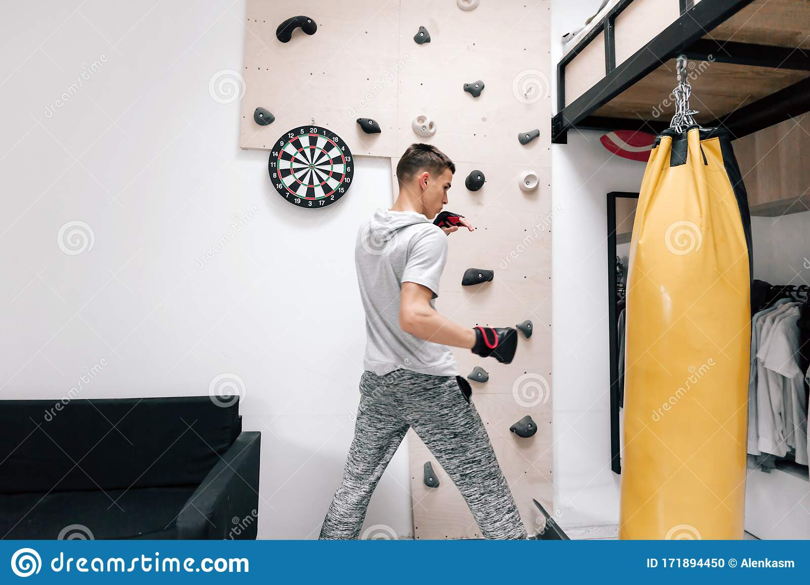 16 17 Years Old Teenage Boy Workout With Boxing Bag In Home Gym