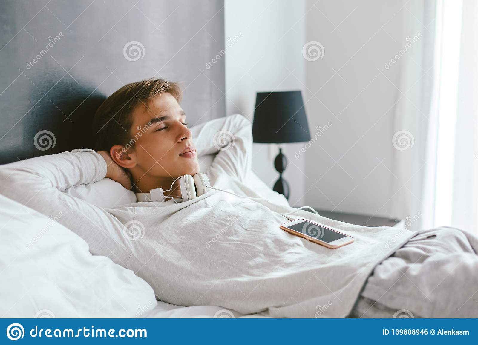 16 Years Old Teenager Relaxing On Bed In His Room Stock Photo Image Of Music Indoor 139808946