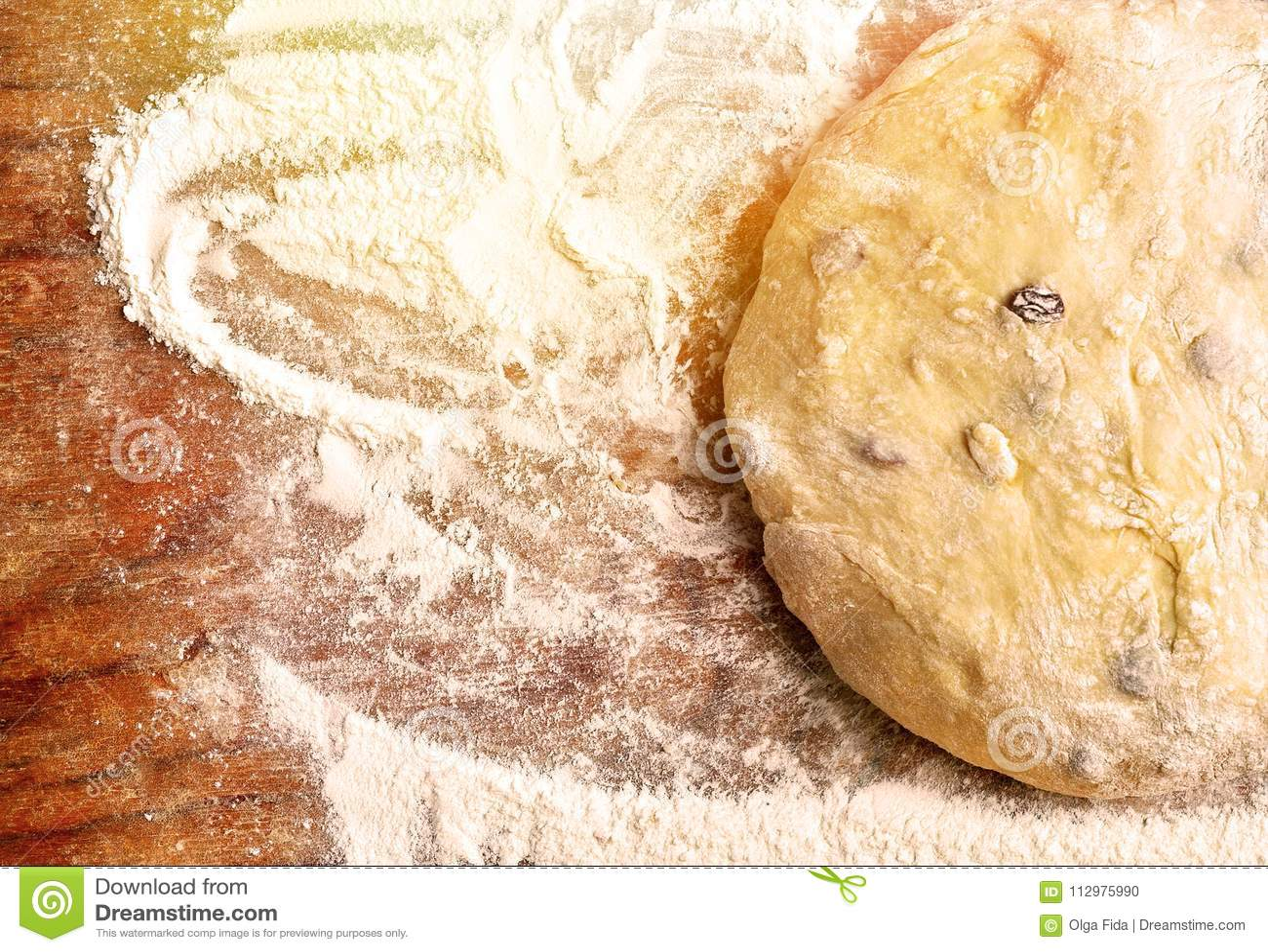 Yeast dough with raisins in flour