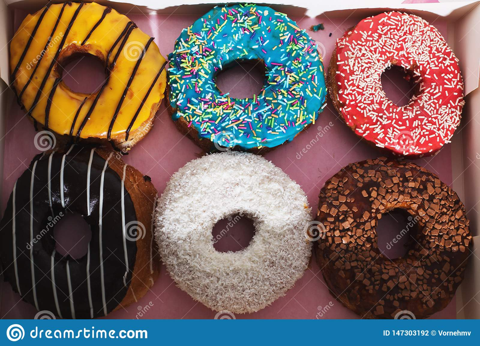 Yellow, blue, red, white and brown donuts with colorful sprinkles in a box next to each other