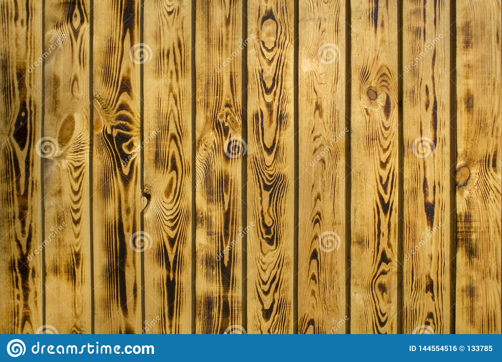 Yellow brown fence wall of natural wooden boards. vertical lines. rough surface texture