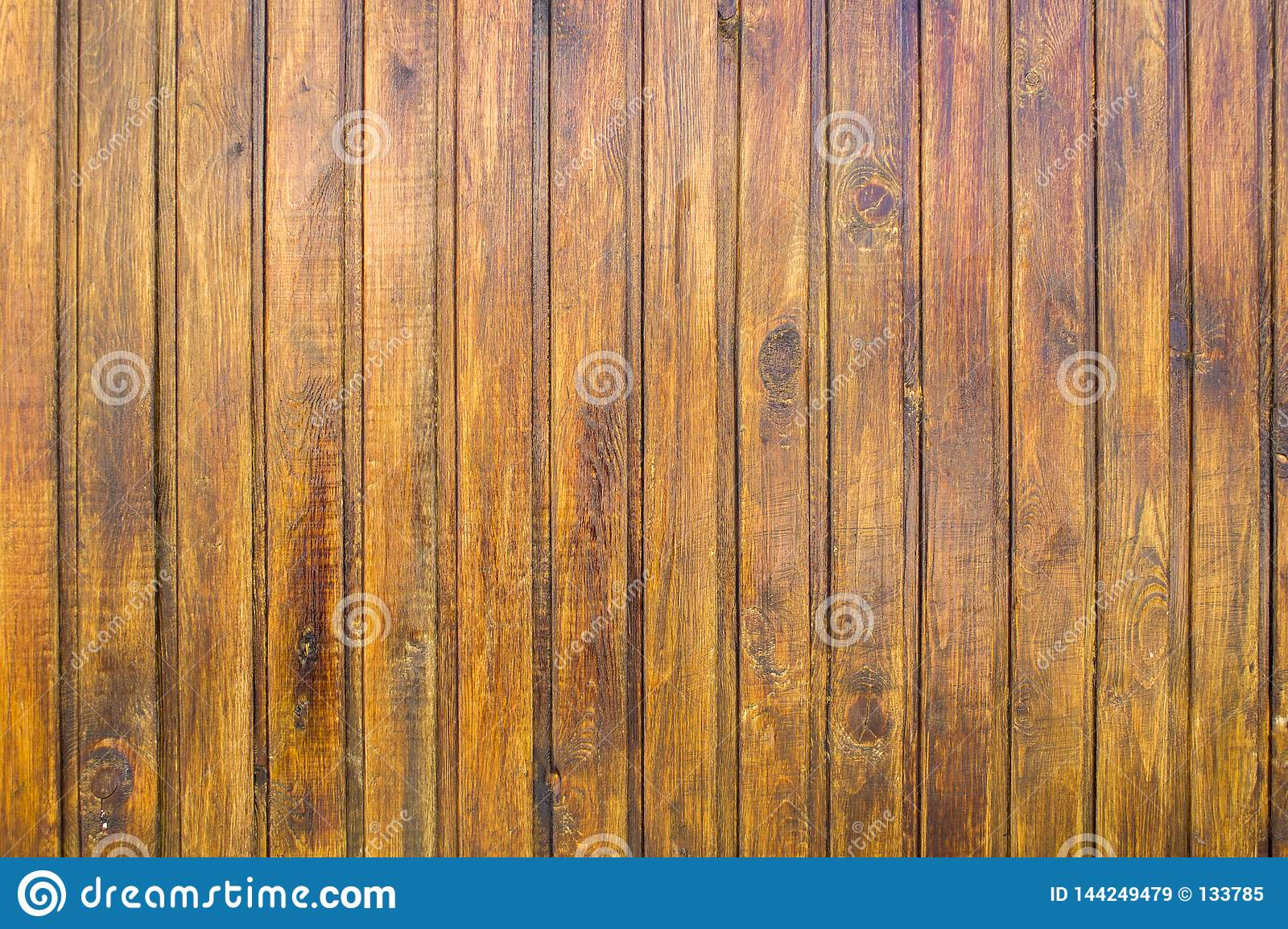 Yellow brown fence wall of wooden planks. vertical lines. rough surface texture