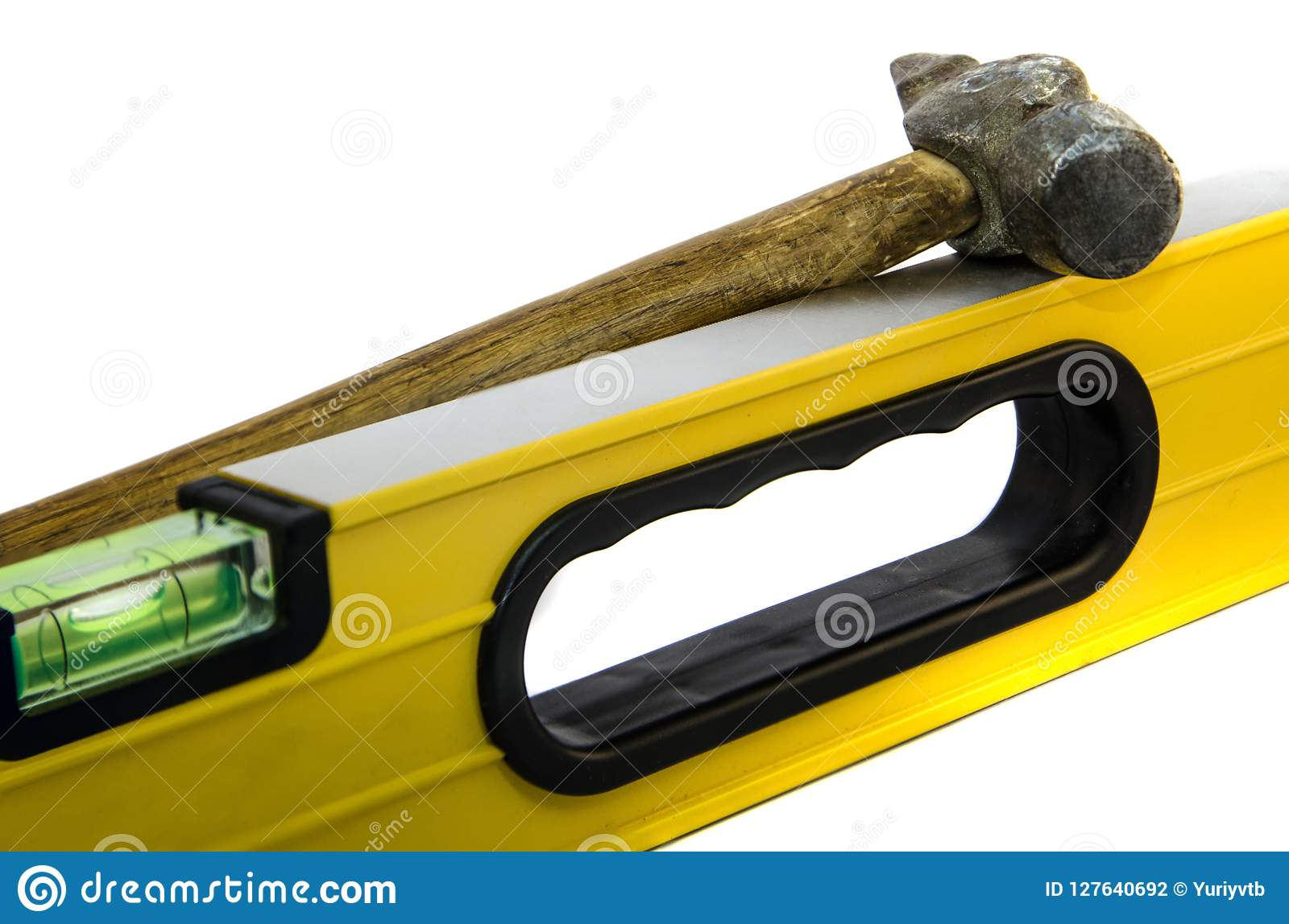 Yellow building ruler with a hammer on a white background