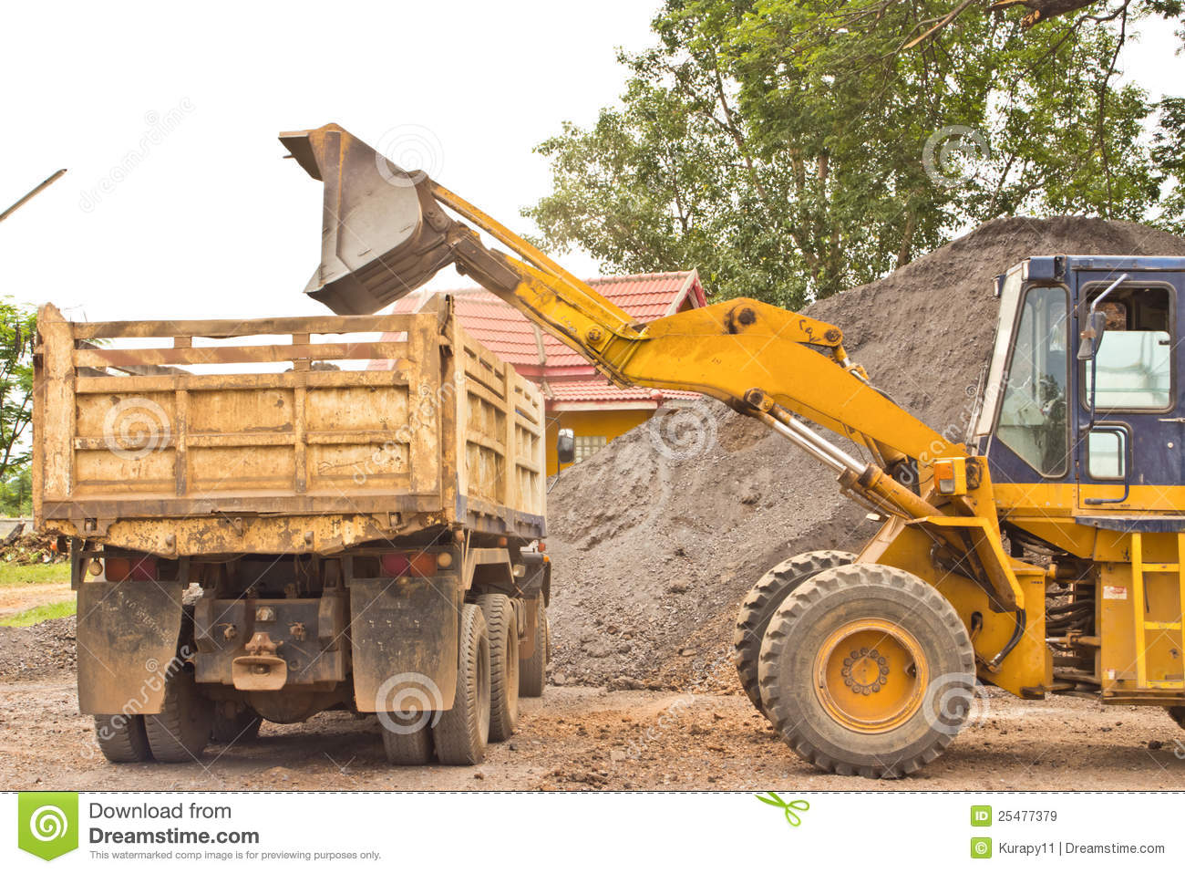 yellow bulldozer was scooping soil into the truck stock image