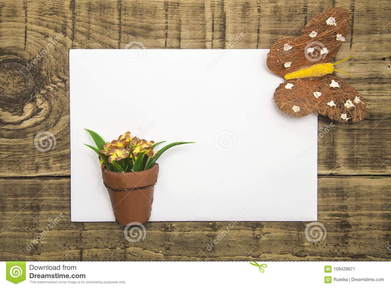 Yellow butterfly and flowers with white paper, copyspace on a wooden background. concept of summer, greeting card, banner, flyer.