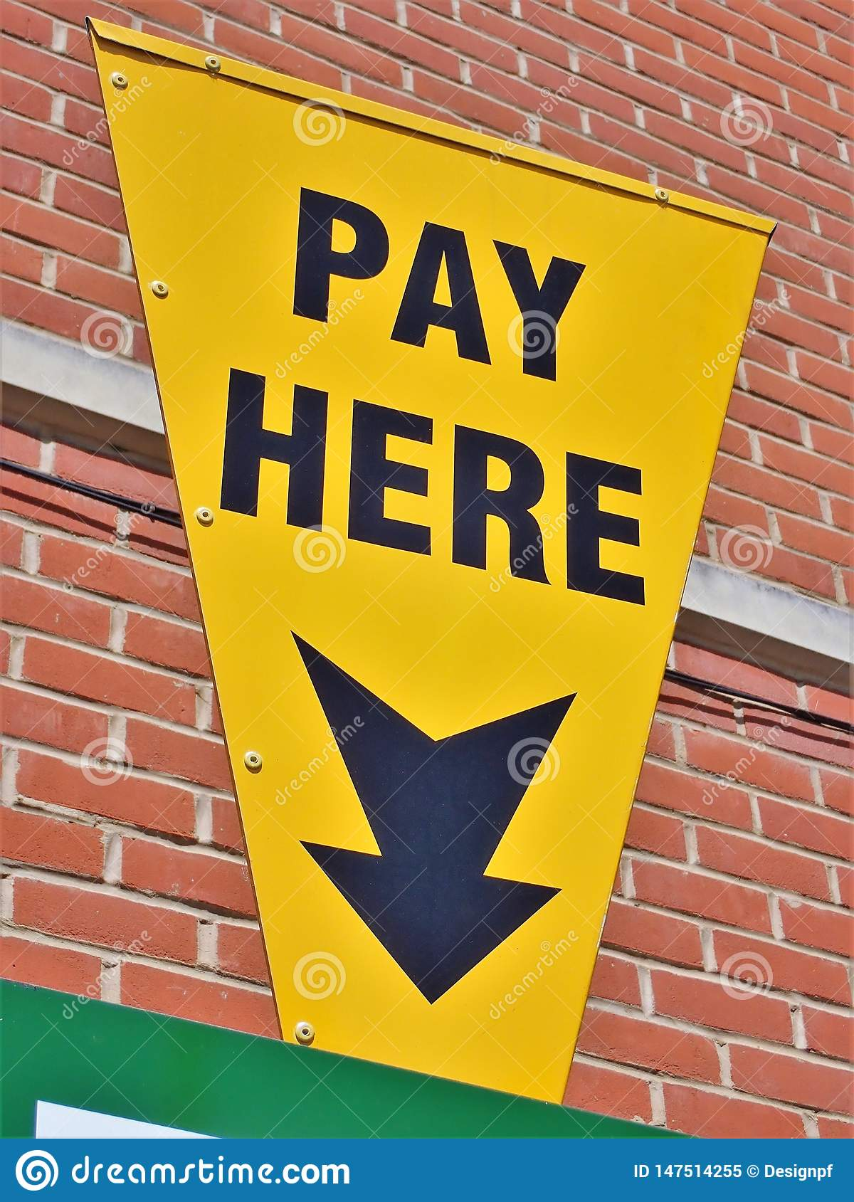 Yellow car parking sign with an arrow and text pay here