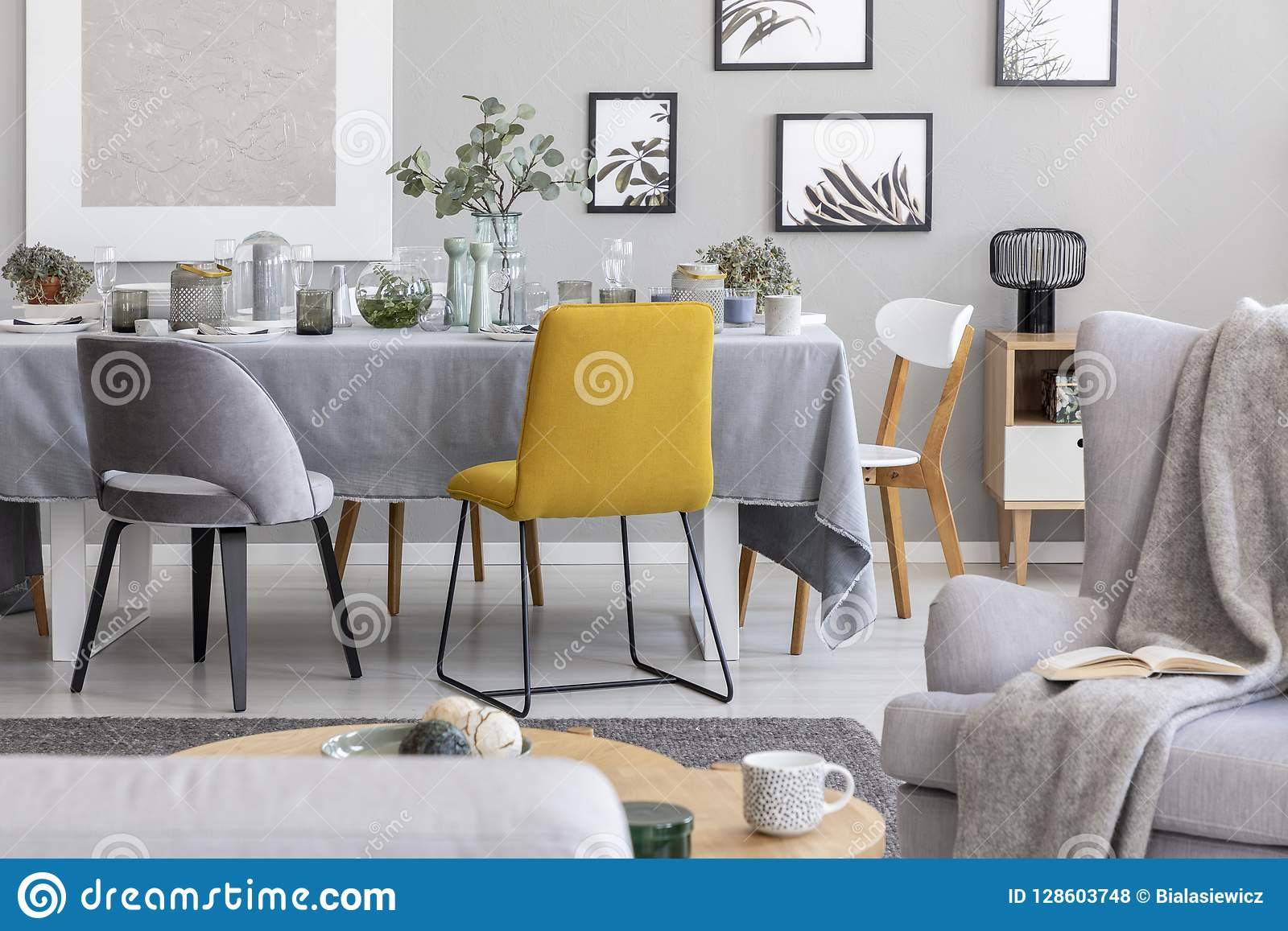 Yellow Chair Next To A Table In A Grey Dining Room Interior