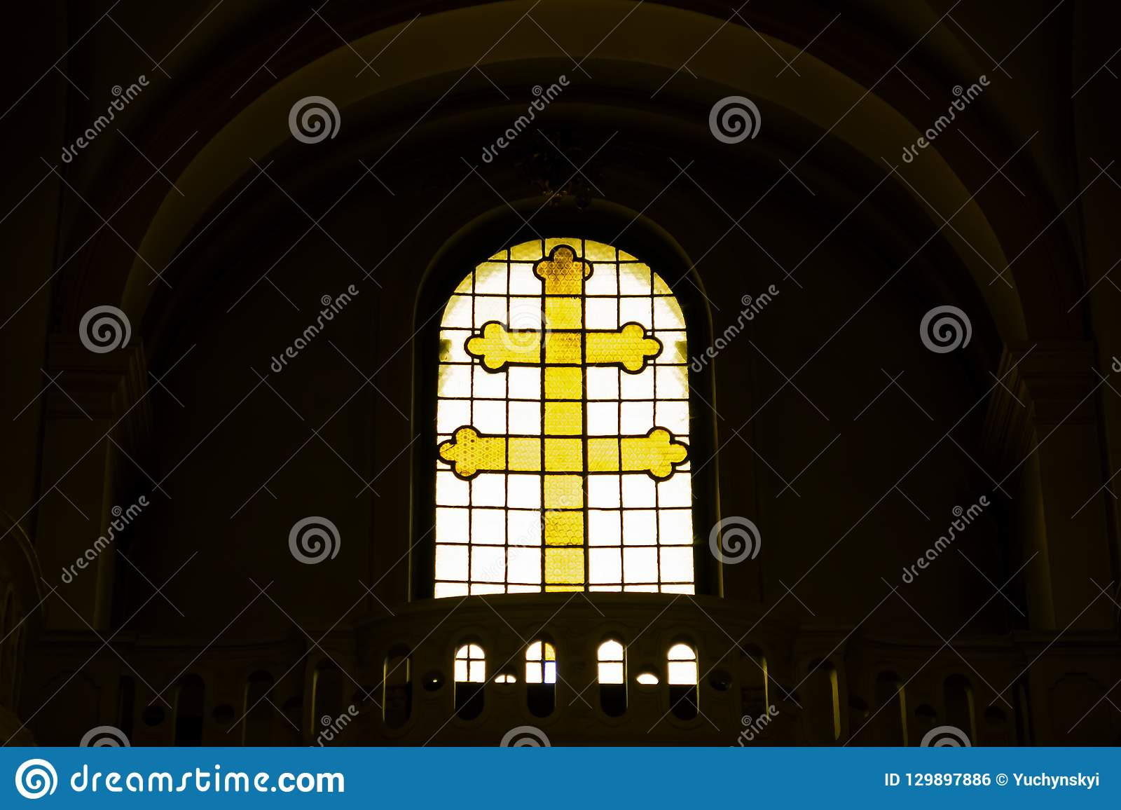 Yellow Christian cross made of glass in the window. Symbols of faith. Crucifixion of Jesus