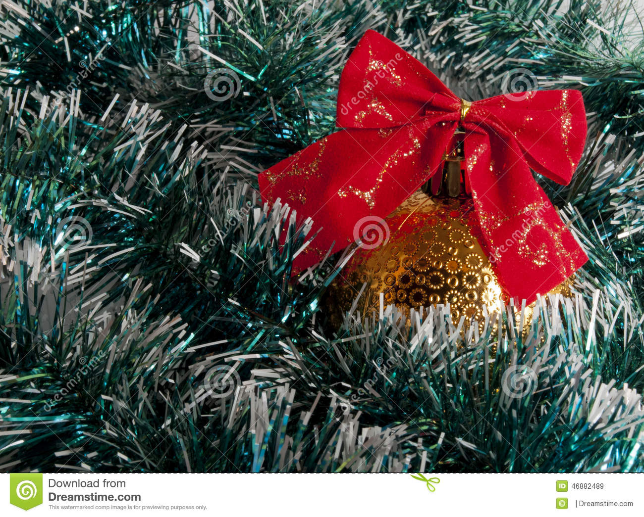 Yellow christmas ball with red bow in green tinsel stock for Red and yellow christmas tree
