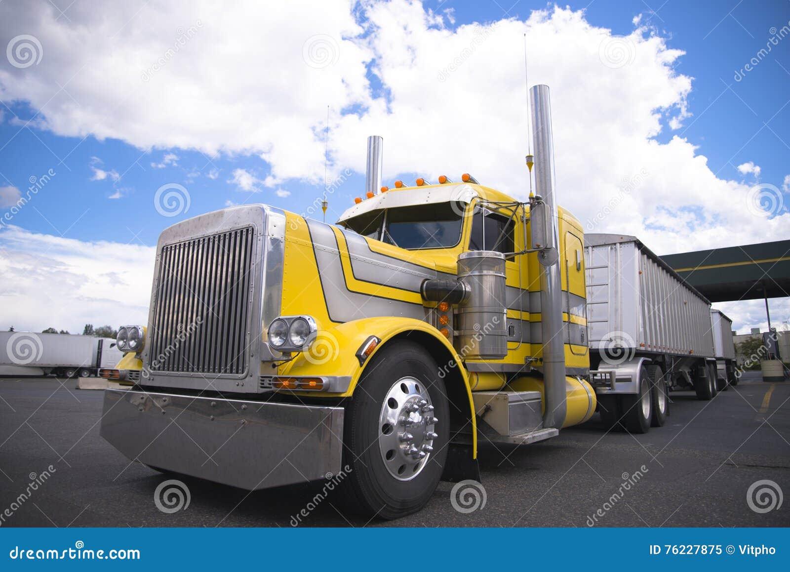 Yellow classic custom semi truck with two bulk trailers