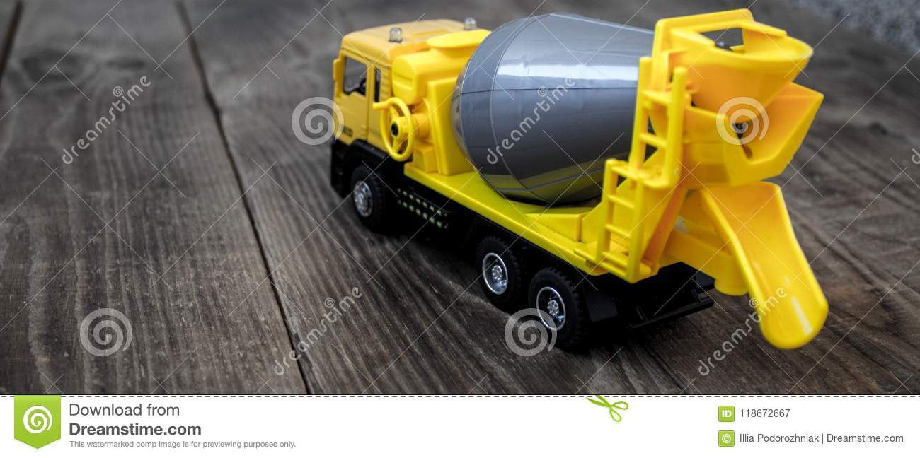 Yellow concrete mixer on a wooden background