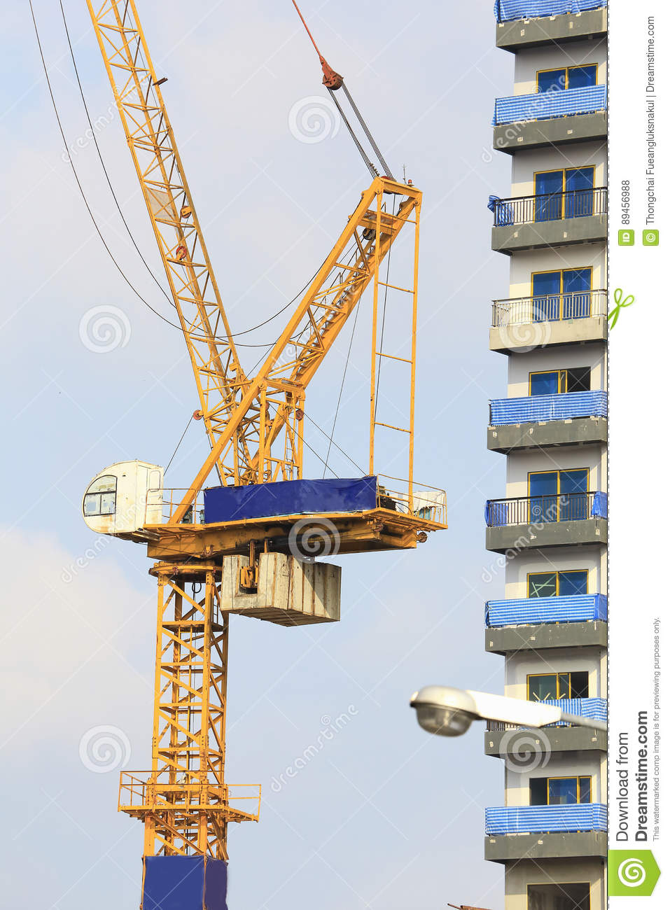 Yellow cranes in construction site with blue sky and cloud.