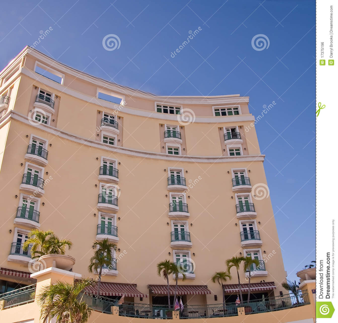 Yellow curved hotel with green balconies royalty free for Hotels with balconies