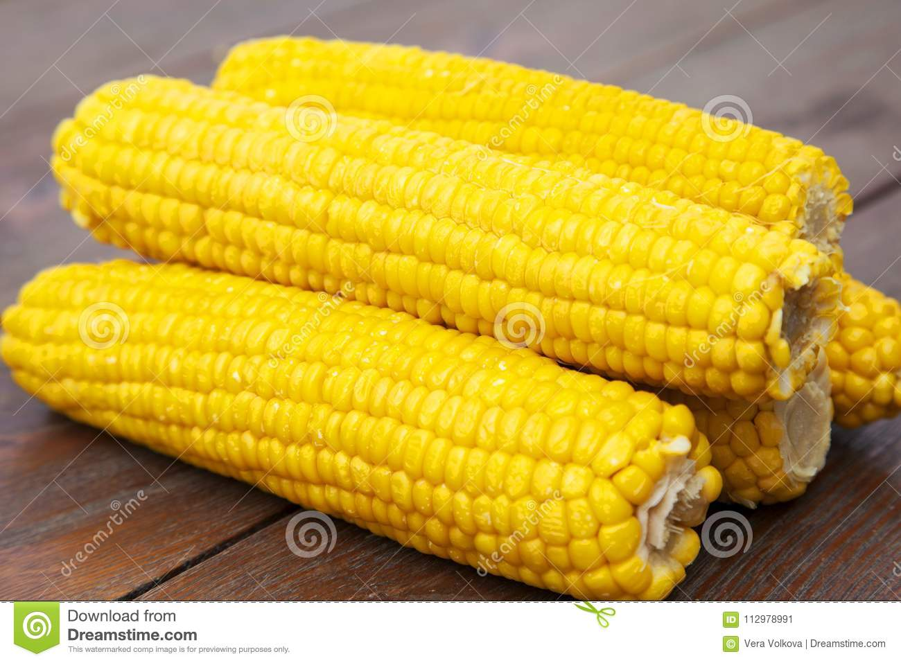 Yellow and delicious cobs on wooden table