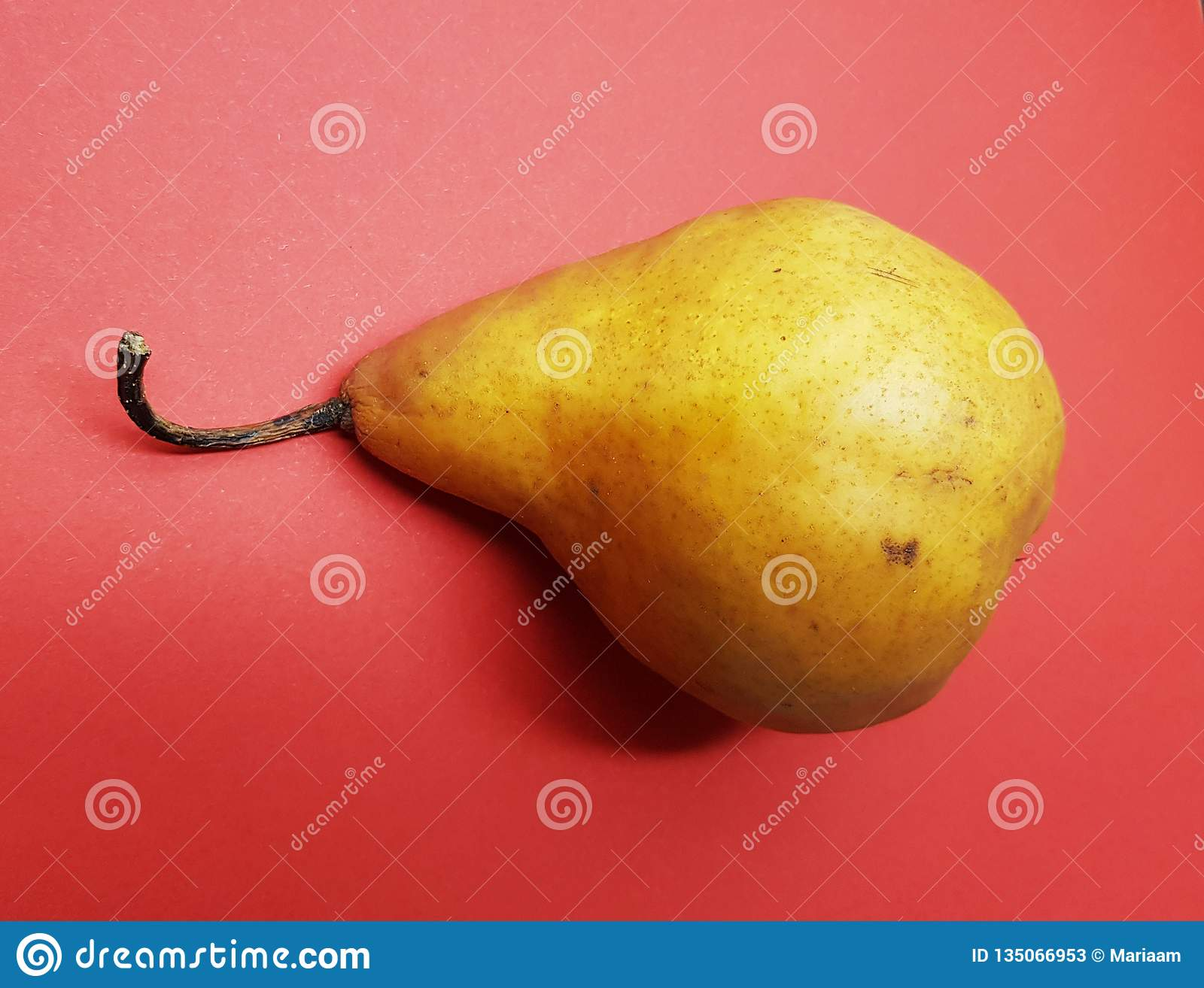 Yellow delicious pear over red background. Healthy pears.