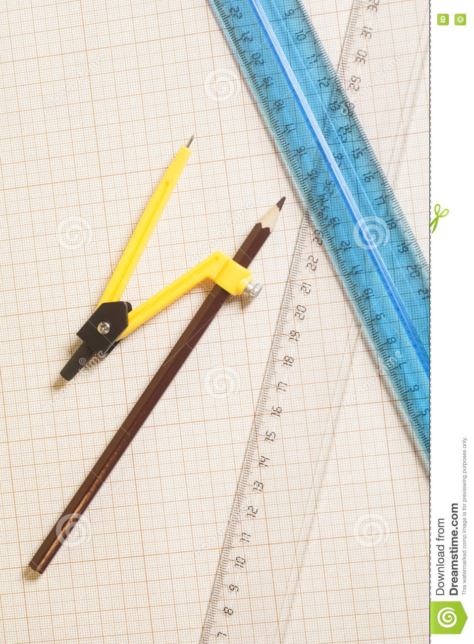 Yellow Drawing Compass With Black Pensil And Rulers On Graph Pa
