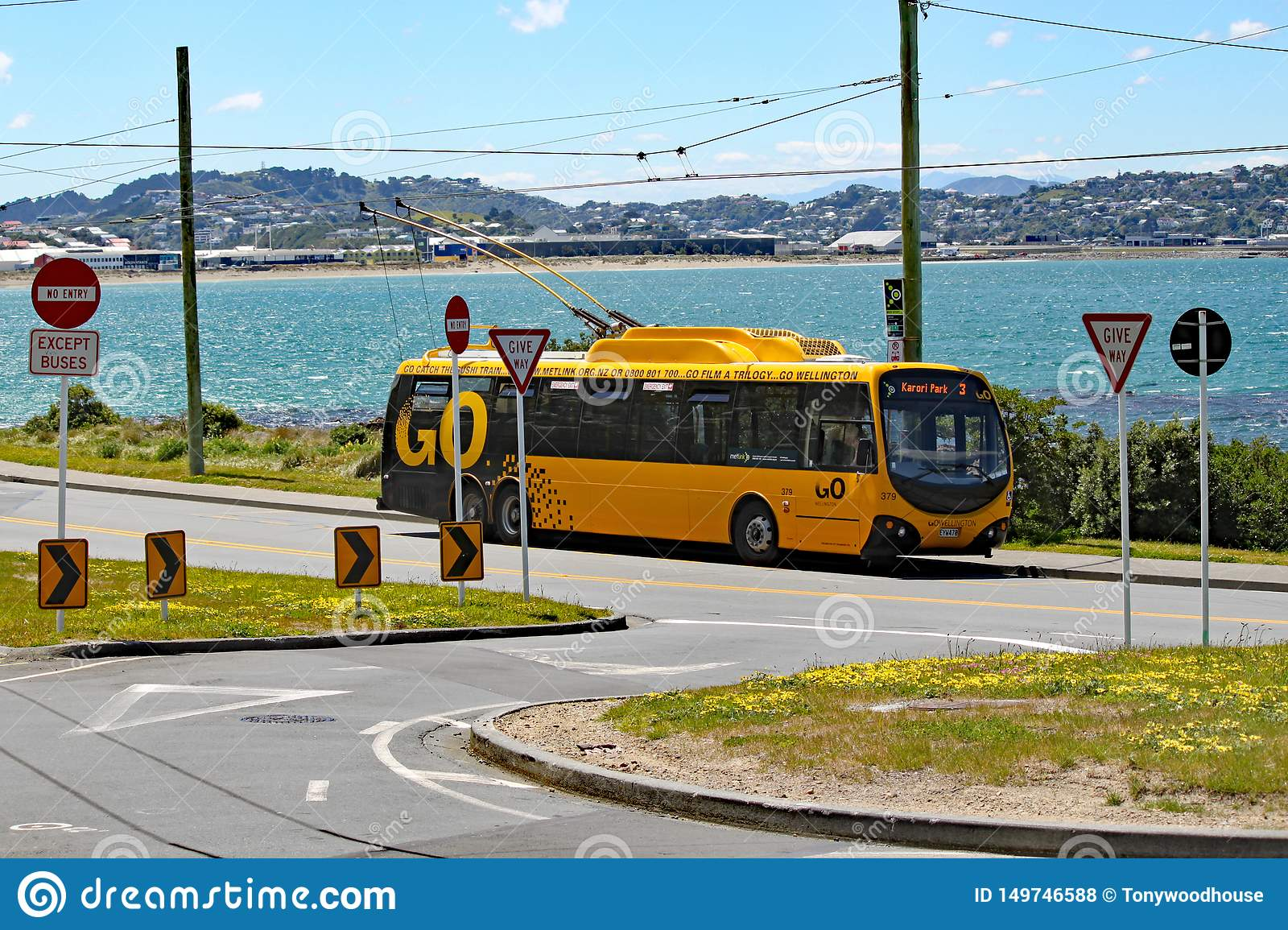 A yellow electric bus waits at the terminus by the side of Lyall Bay, Wellington, New Zealand