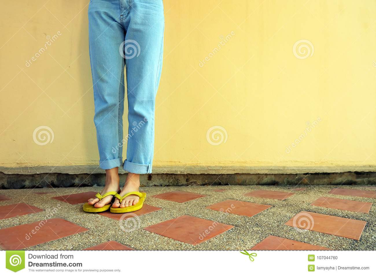49b149d03184 Yellow Flip Flops. Female Wearing Sandals and Blue Jeans Standing on Tile  Floor