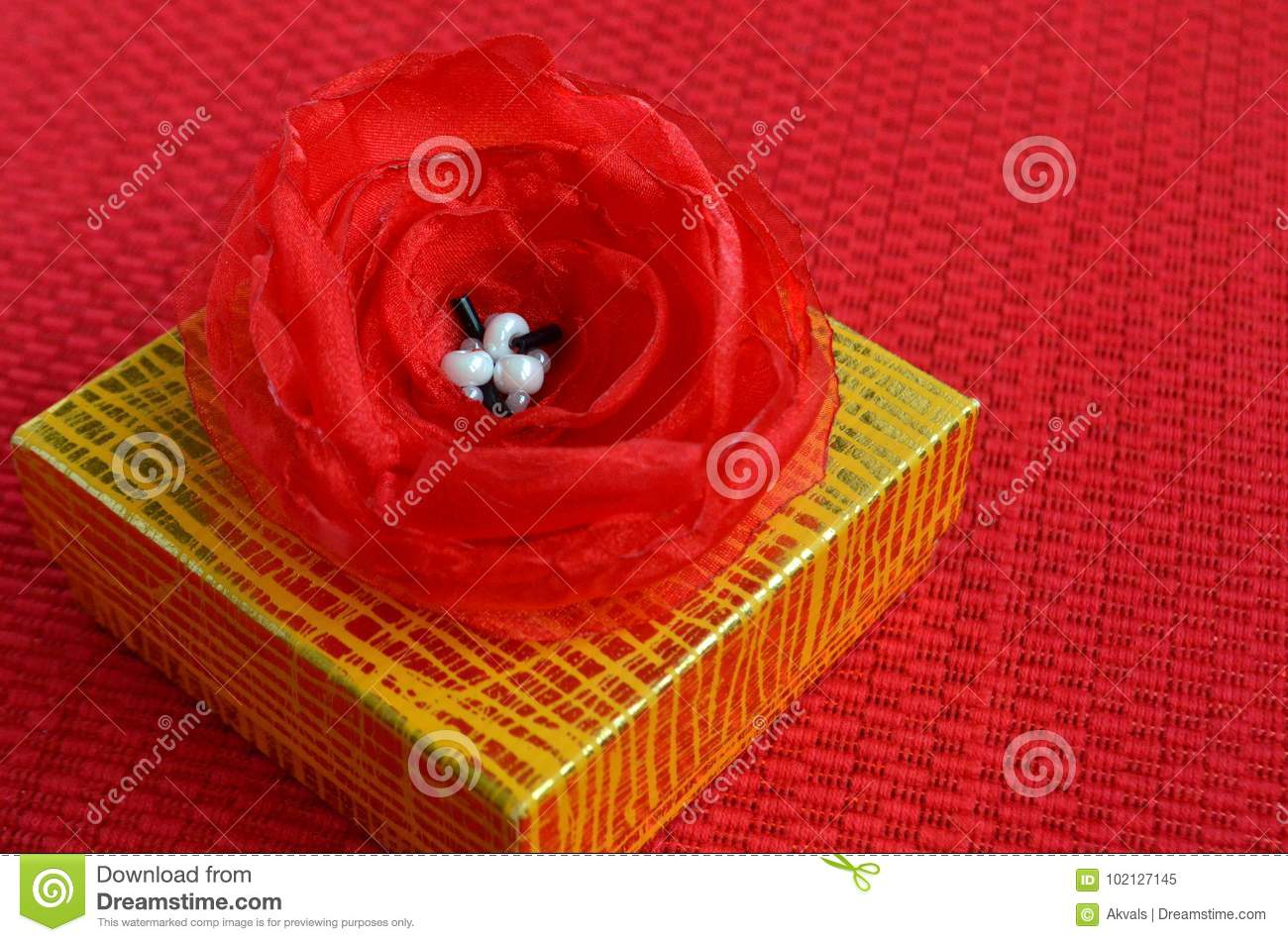 Yellow Gift Box With Red Fabric Flower Decoration Close Up Stock