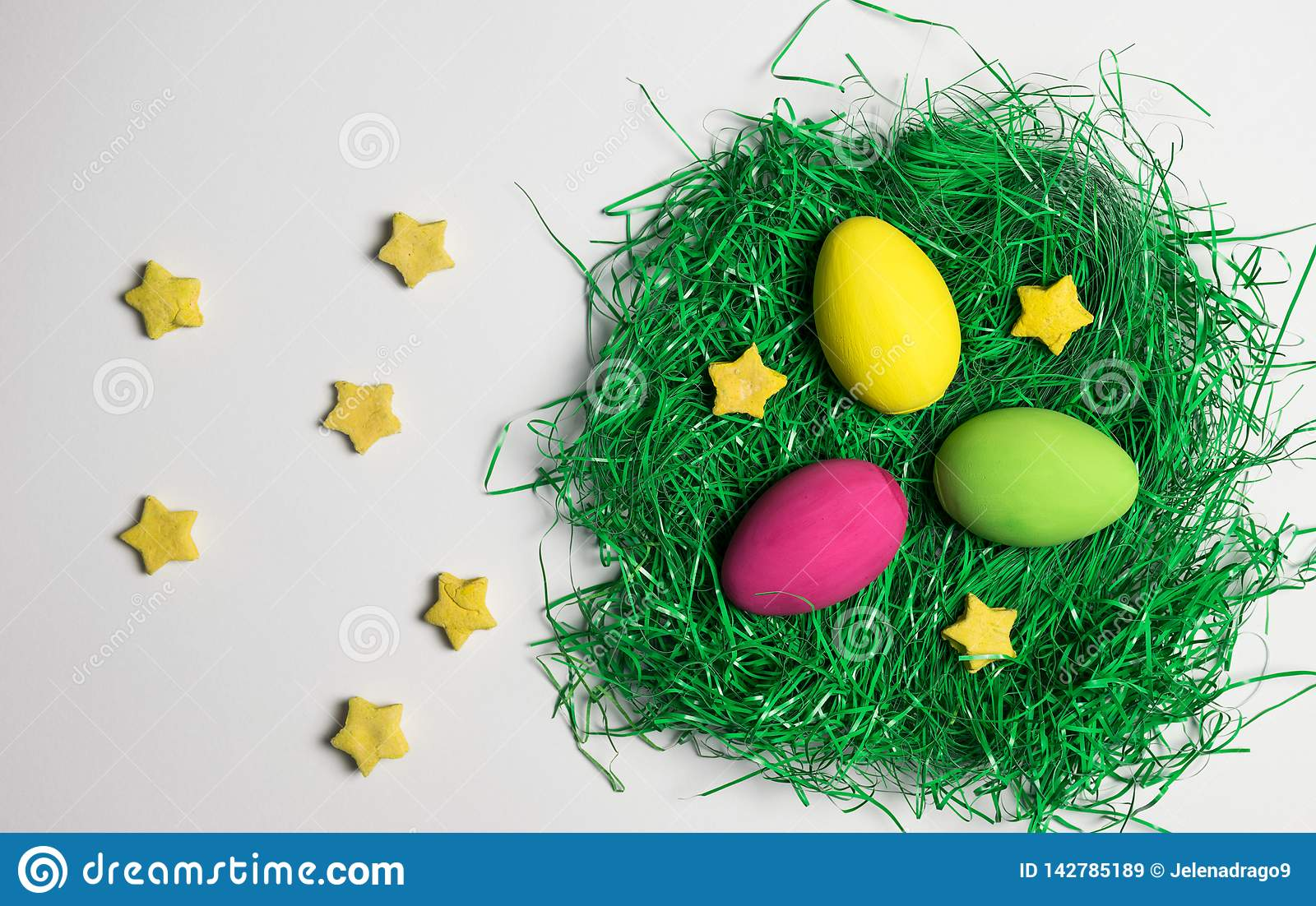 Yellow, green and pink Easter egg in nest of artificial green grass with yellow decorative stars all over white background.